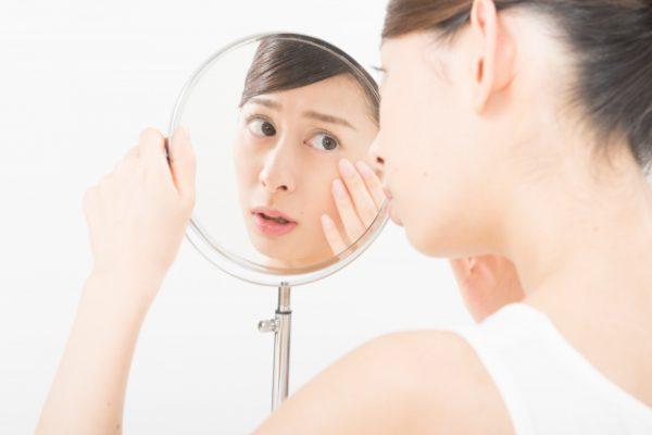 顔のトラブルを気にして鏡を見ている女性