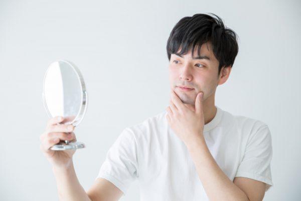 髭を気にして鏡を見る男性